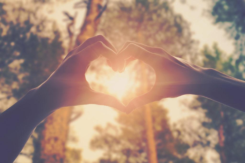 Zwei Hände formen ein Herz, durch das die Sonne scheint
