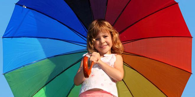 Kleines Mädchen mit einem aufgespannten Regenbogenschirm